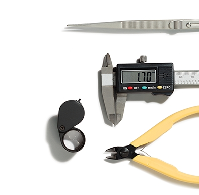 Caliper, loupe, stone tweezers, and pliers