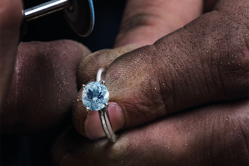 Jeweler polishing white gold ring with blue stone